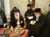 His Beatitude offers a piece of cake to Archimandrite Bartholomew